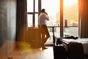 Image of man looking out of hotel room on sunny day